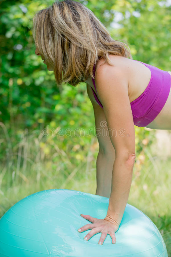 The hamstring curl exercise. A woman with hands on the ball performing the hamstring- curl exercise royalty free stock photo