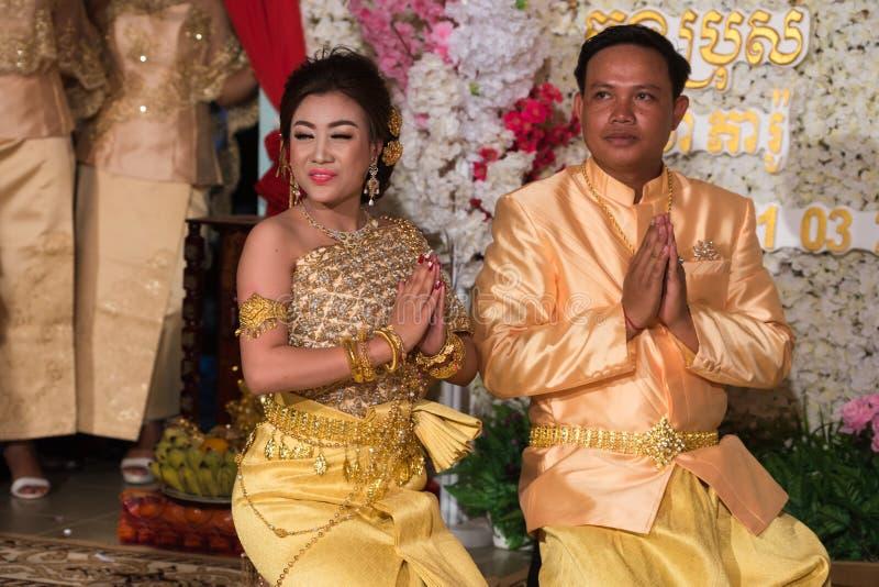 Han fästmöpar tackar till deras föräldrar som framme knäfaller av dem royaltyfri fotografi