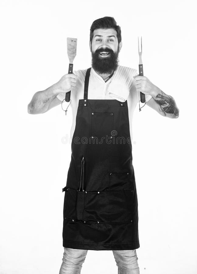 Han ?r en stor kock Lycklig gallerkock med matlagningredskap Sk?ggig maninnehavgaffel och spatel f?r att laga mat och att tj?na s arkivbild