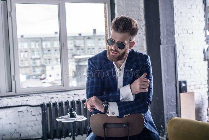 Han ska sm?lta din hj?rta Dräkt och eyewear för stilig ung skäggig man som oavkortad bort ser, medan sitta på stolen royaltyfria bilder