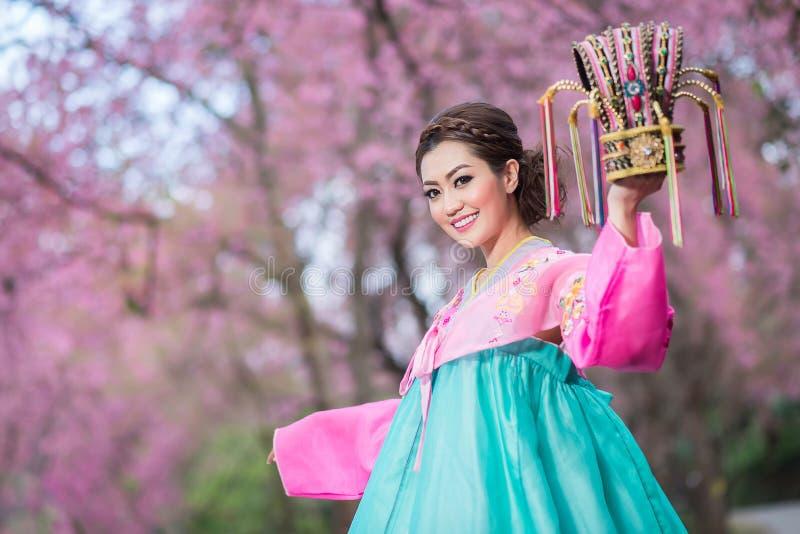 Hanbok: de traditionele Koreaanse kleding en de mooie Aziatische meisjesholding overbevolken met sakura stock afbeelding