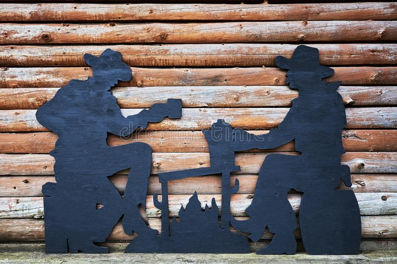 Two men drinking coffee wooden caricature. Hanceville, British Columbia, Canada - July 4, 2012: Wooden caricature of two country men drinking coffee in front of royalty free stock image