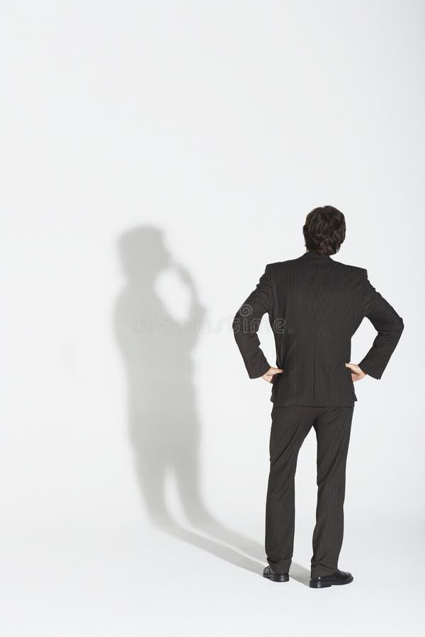 Hanches de With Hands On d'homme d'affaires discutant sa propre ombre images libres de droits