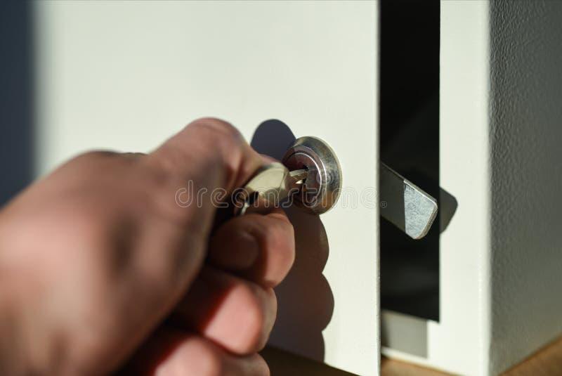 Hand öffnet den Schlüssel zum Verschluss des weißen Safes auf dem Bürotisch lizenzfreies stockfoto