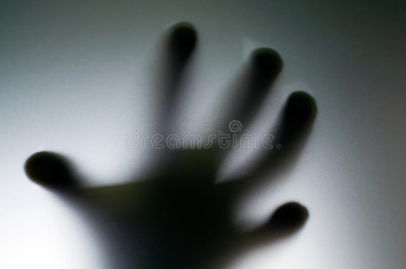Hand. A scary hand behind glass stock photos