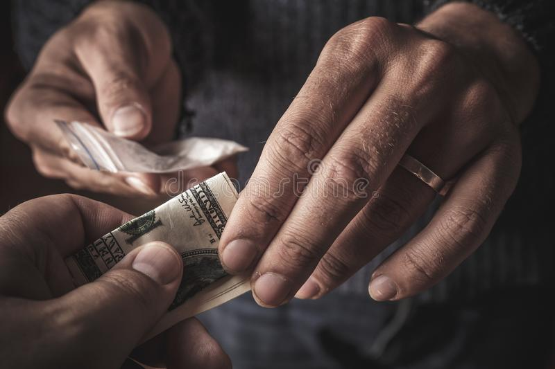 Hand of addict man with money buying dose of cocaine or heroine or another narcotic from drug dealer. Drug abuse and traffic stock photo