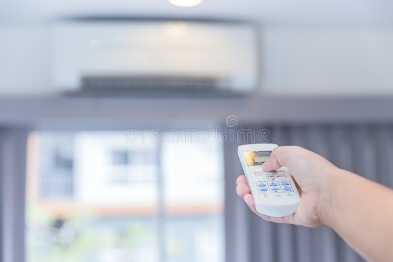 Adjust AC temperature with remote control to wall type air conditioning. Hand adjust AC temperature with remote control to wall type air conditioning home royalty free stock image