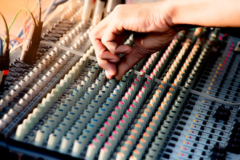Hand adjusting audio mixer control music,music equipment for sound mixer control, electronic device. Hand adjusting audio mixer control music,music equipment stock photo