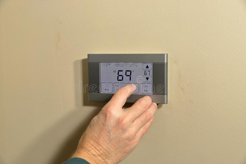 Hand adjusting temperature on thermostat stock image