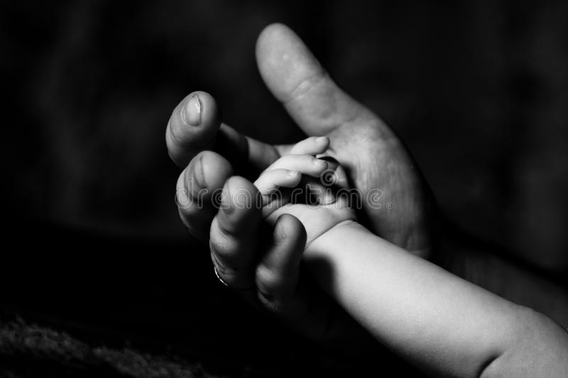 Hand of an adult and child. In dark vein royalty free stock photography
