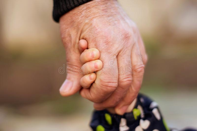 Hand of an adult man holding tightly child hand. Family connection, kid safety, protection and anti kidnap concept royalty free stock images