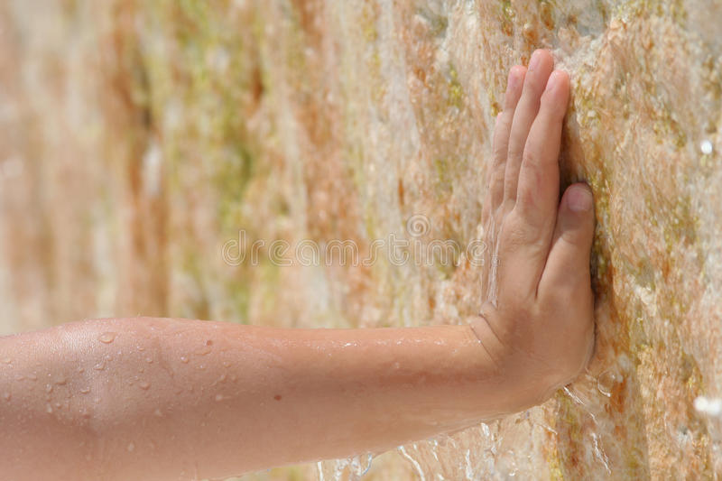 Hand against a stone wall with dripping water stock photography