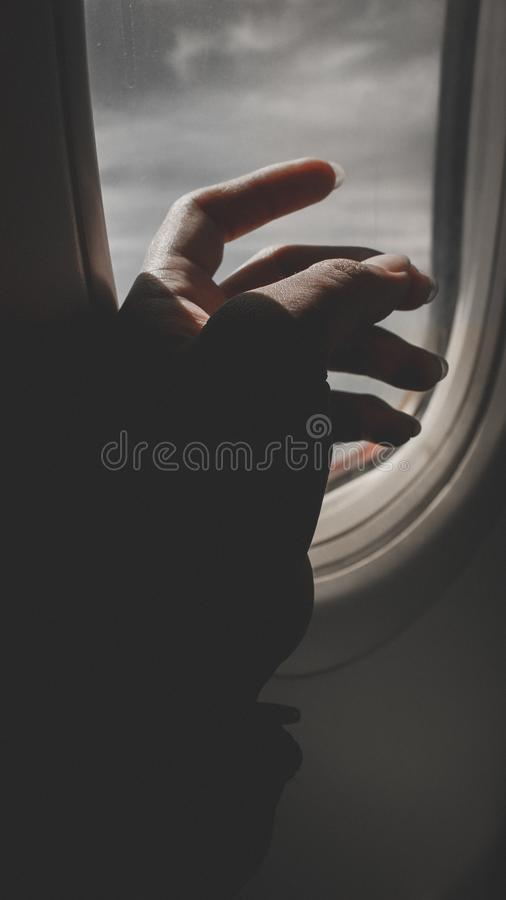 Hand By Airplane Window stock image