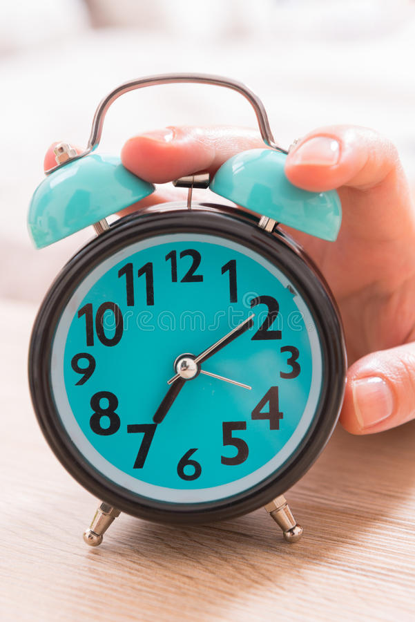 Hand on the alarm clock royalty free stock image
