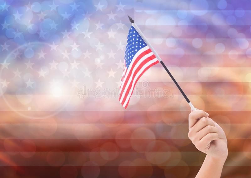 Hand with American flag with sparkling light bokeh background. Digital composite of Hand with American flag with sparkling light bokeh background royalty free stock photos