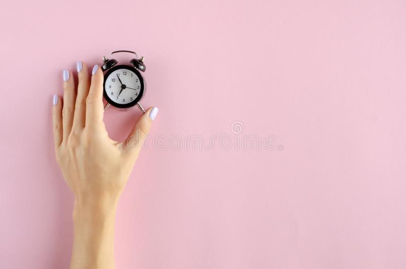 Hand with analog alarm clock composition on pink background stock images