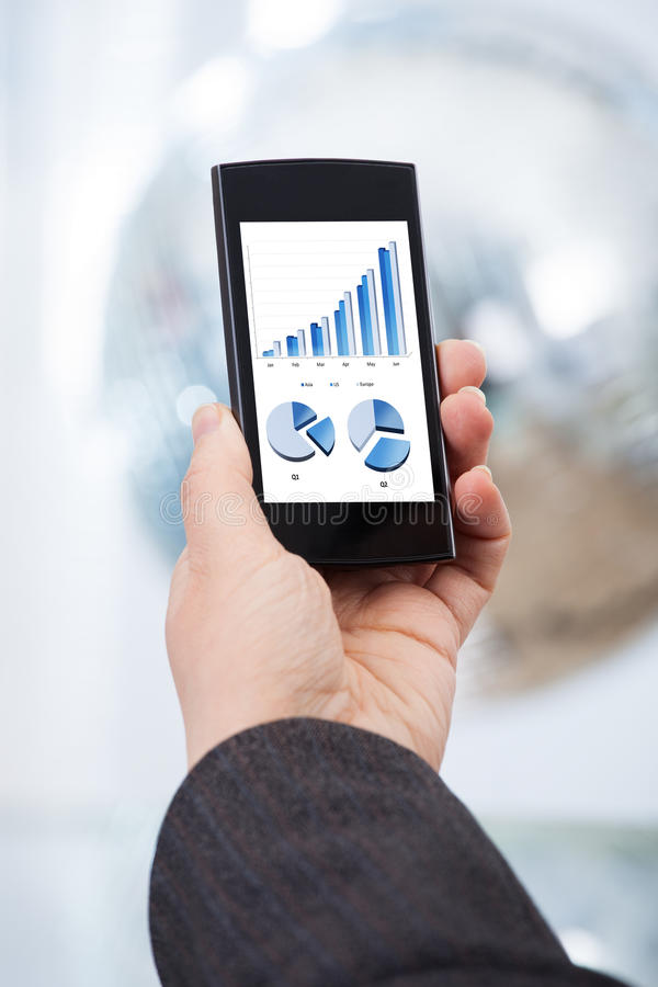Hand analyzing financial charts on smartphone royalty free stock images