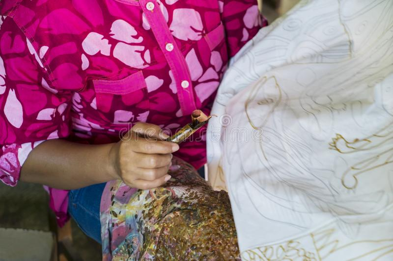 Anonymous woman making batik on a fabric. Hand of anonymous woman using a canting and wax for making batik on a fabric royalty free stock images