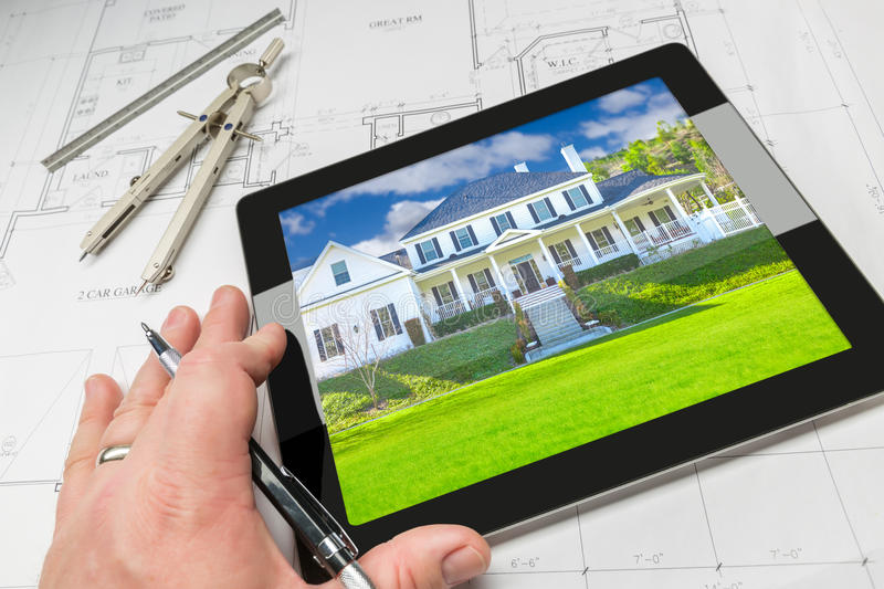 Hand of Architect on Computer Tablet Showing Home Photo Over Hou stock photography