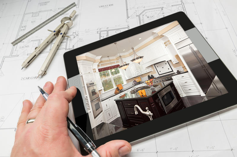 Hand of Architect on Computer Tablet Showing Kitchen Photo Over royalty free stock photo