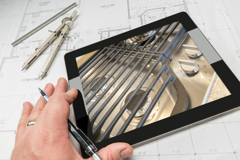 Hand of Architect on Computer Tablet Showing Stove Details Over stock photo