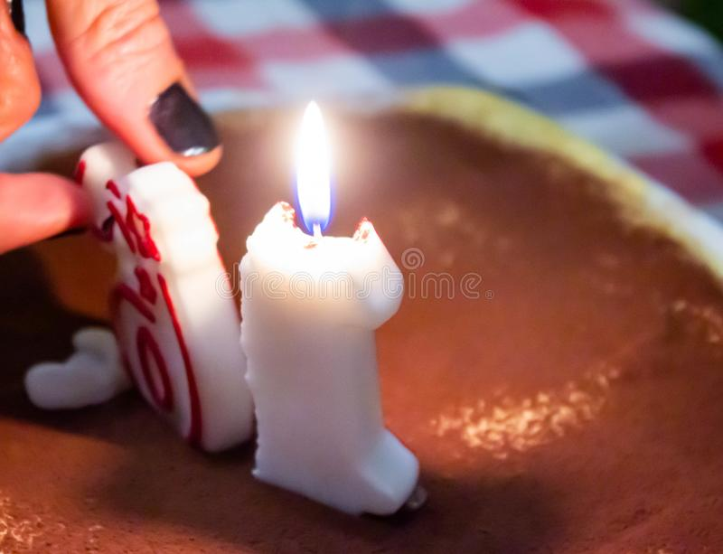 Hand arranging birthday candles on cake, one of the candles is lit. stock image