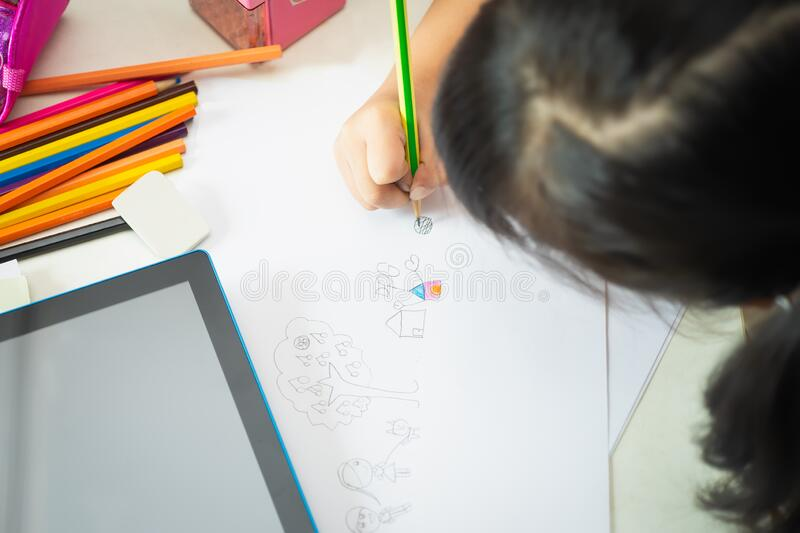 Hand of Asian little girl is writing or drawing with pencil on blank paper sheets on the table at school .selective focus stock photos