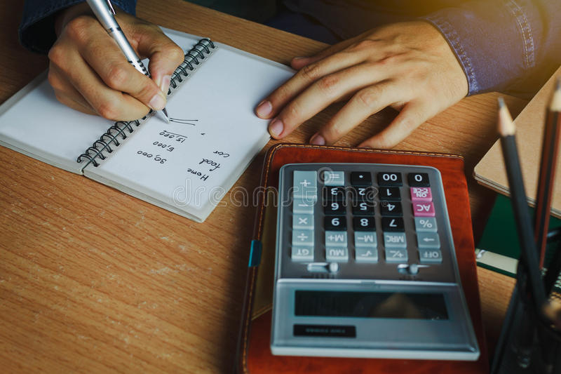 Hand Asian man calculate finances and accounting for monthly expenses / charges or cost. On notebook with accessories in home office room.Idea to save / stock photos