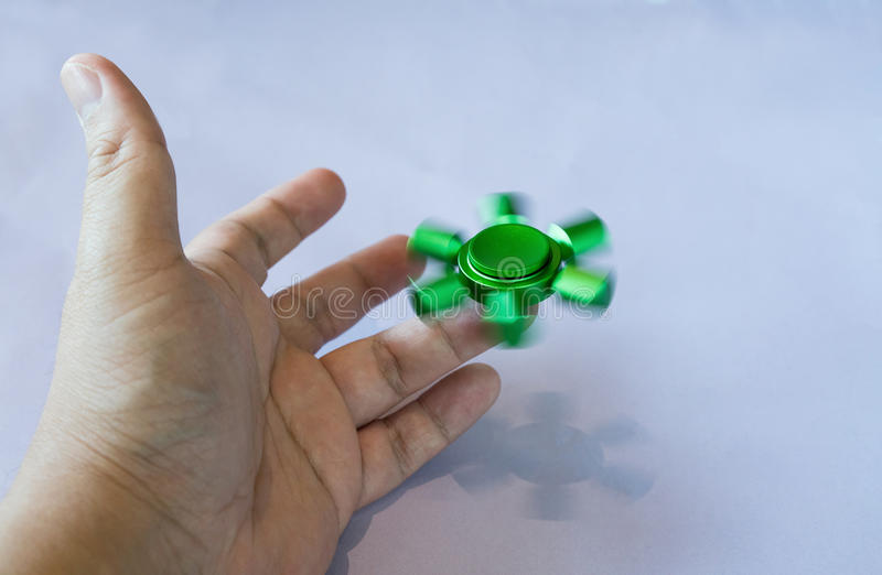 Hand of asian man spins green fidget spinner royalty free stock image