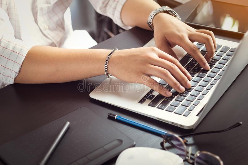Hand of asian men using laptop keyboard with English and Thai alphabets on black table at home office .selective focus royalty free stock photo
