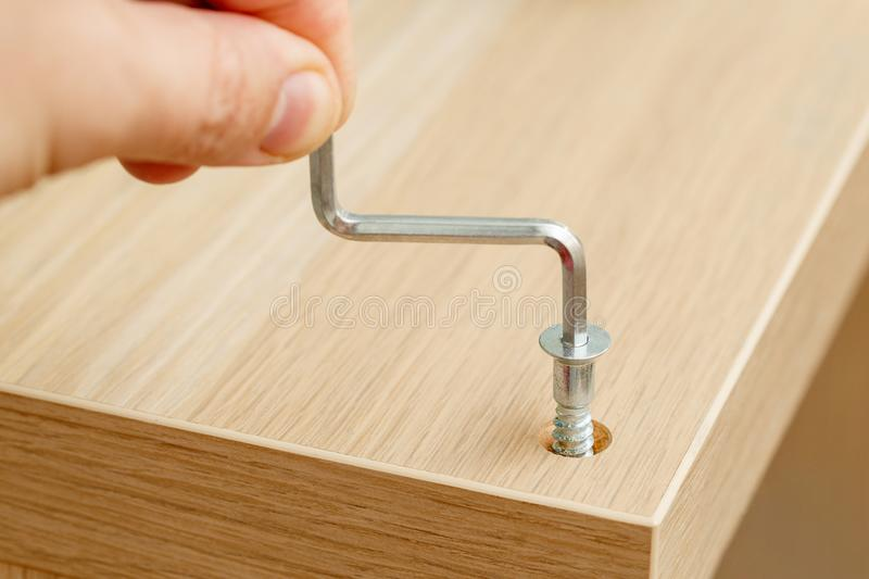 Hand of assembly worker with hexagonal key screwing furniture stock photography
