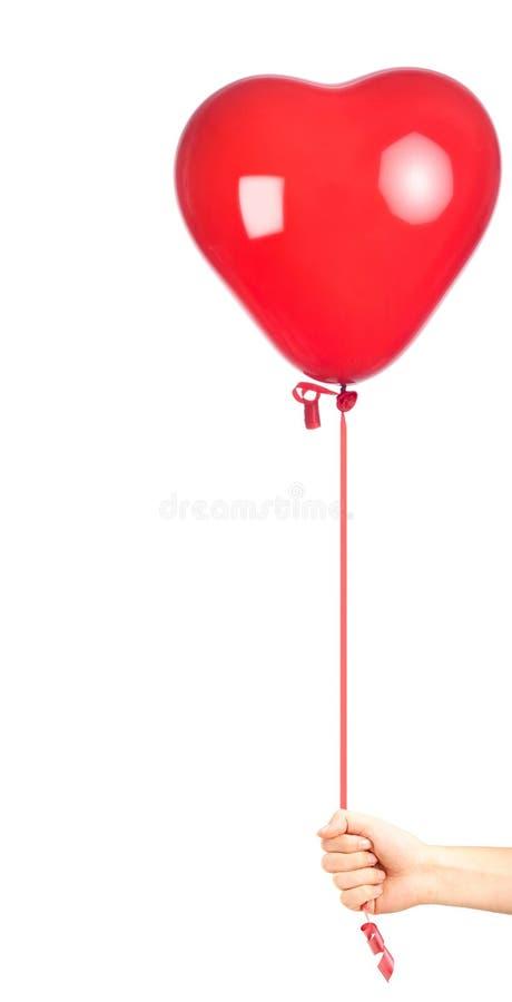 Hand att rymma en hjärta formad röd ballong royaltyfria foton
