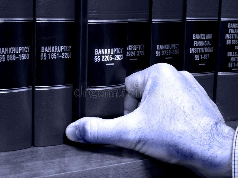 Hand auf Buch auf Bankrott stockbilder