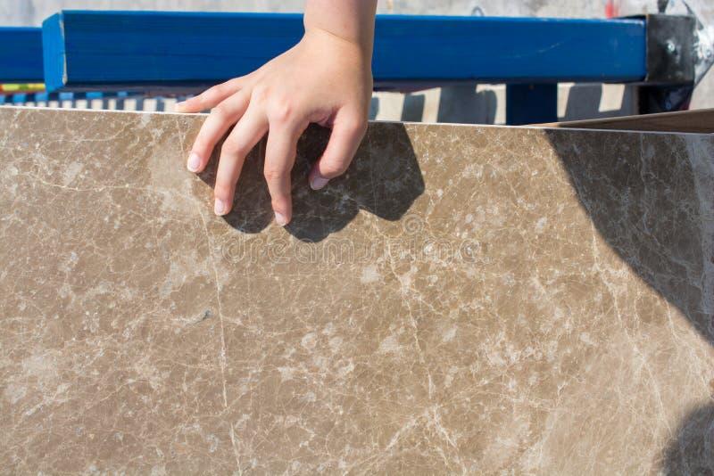 Hand auf Stück des Marmorsteins stockbild