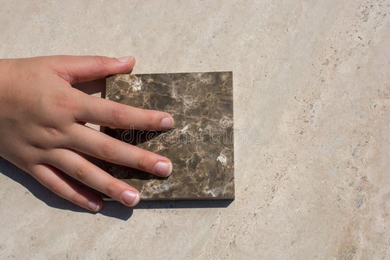 Hand auf Stück des Marmorsteins lizenzfreies stockbild