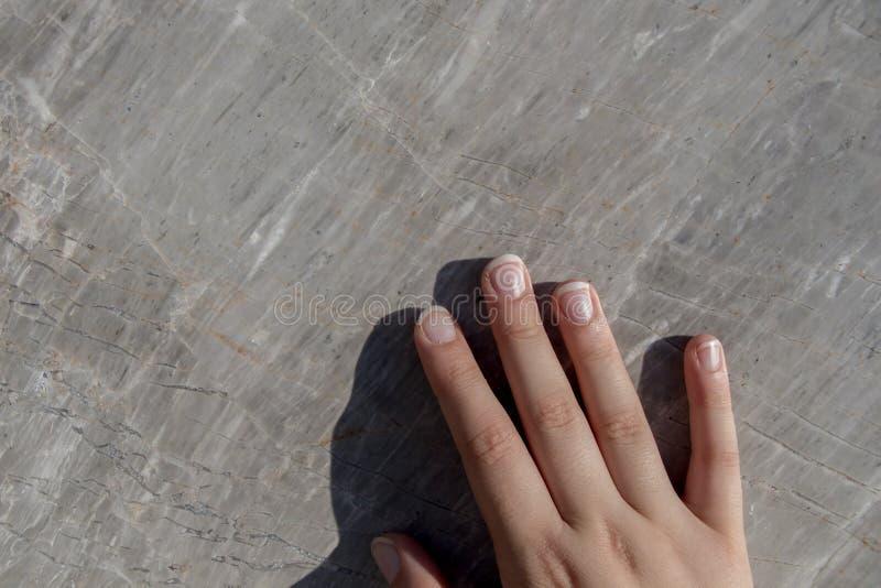 Hand auf Stück des Marmorsteins lizenzfreies stockfoto