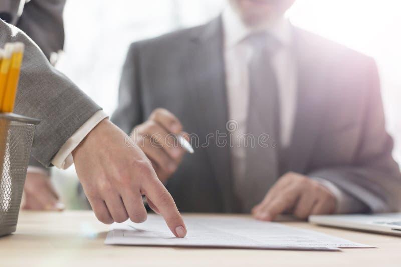 Hand av affärskvinnan som i regeringsställning pekar på dokumentet till den höga affärsmannen arkivfoto
