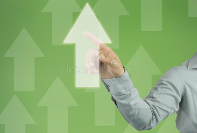 Hand av affärsmanhandlaget till en affärspil på grön backgroun arkivbild