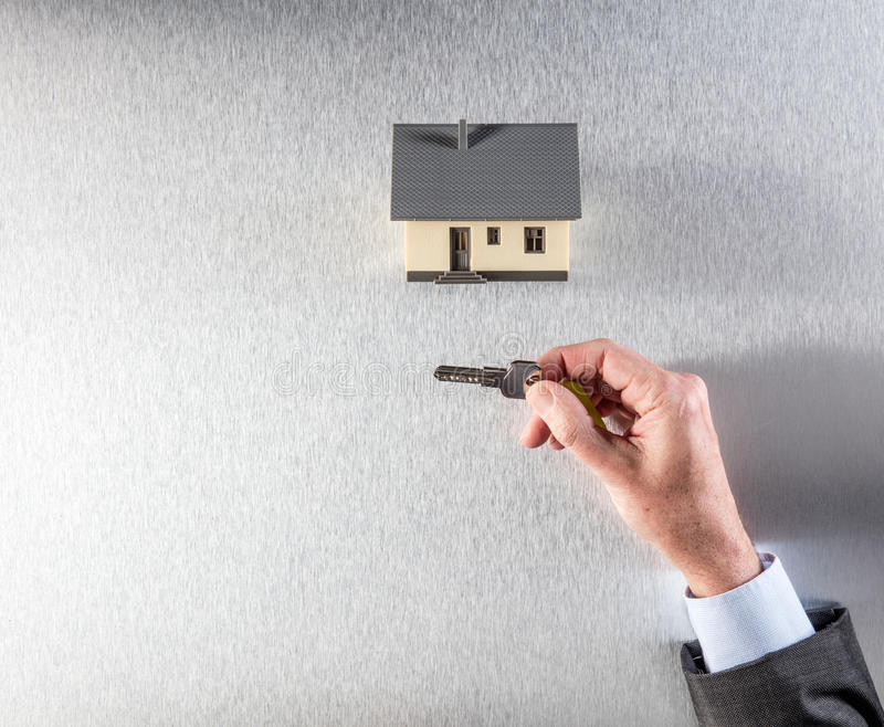 Hand av affärsmannen, den hem- ägaren eller fastighetsmäklaremedlet som ger tangent arkivfoton