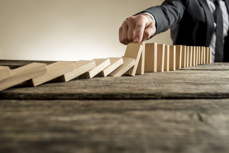 Hand av affärsmannen som stoppar fallande dominobrickastycken royaltyfri foto