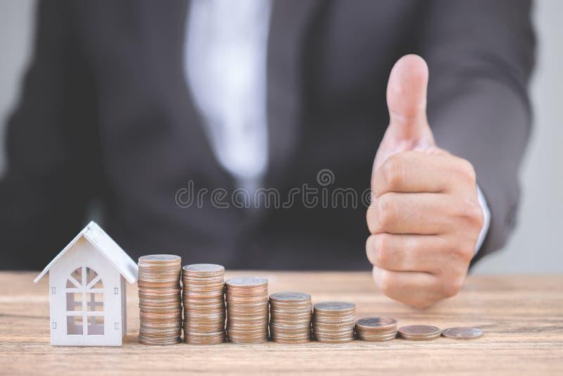 Hand av affärsmanshowtummar upp med pengar av myntbuntmomentet upp växande vitt hus för tillväxt och för modell på tabellen egens arkivfoton