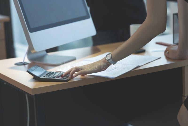 Hand av arbetekvinnan som använder räknemaskinen på kontorsskrivbordet arkivfoto