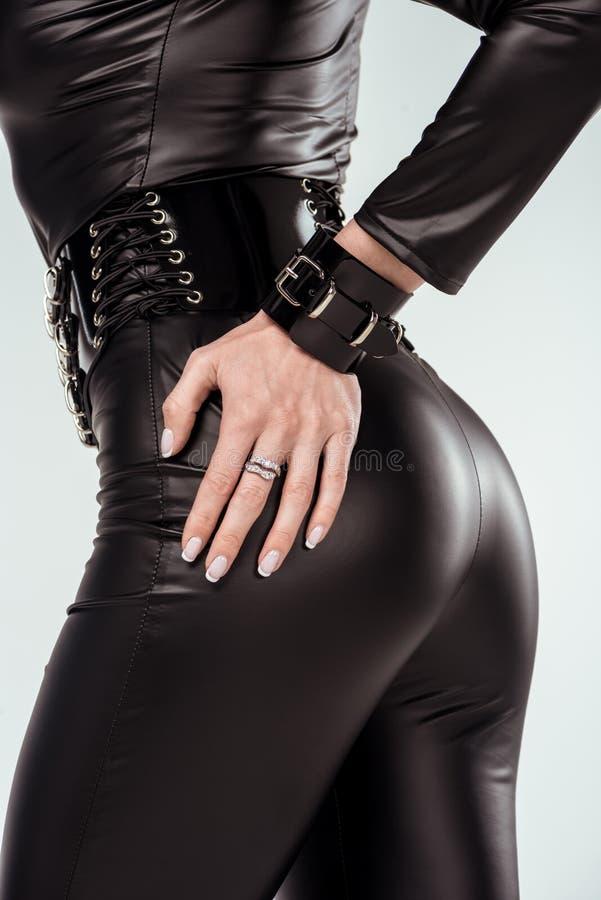 Hand av bakdelar av den attraktiva varma flickan i catsuit fotografering för bildbyråer