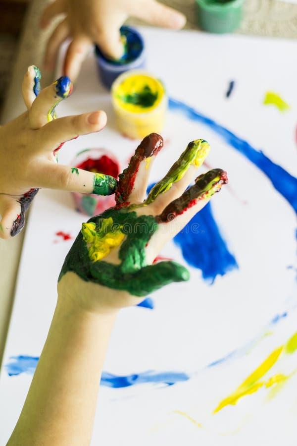 Hand av barnet, medan g?ra fingerpaint royaltyfria bilder