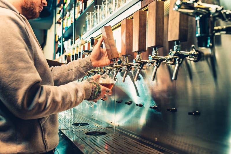 Hand av bartendern som häller ett stort lageröl i klapp royaltyfri foto