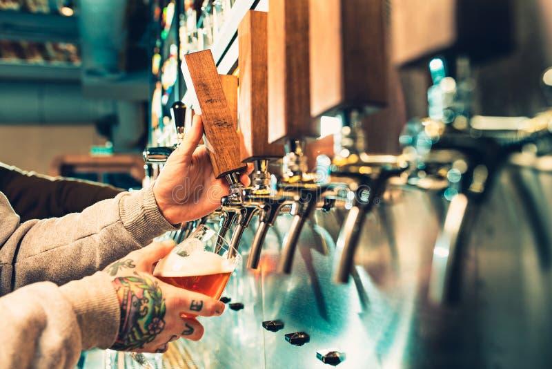 Hand av bartendern som häller ett stort lageröl i klapp royaltyfria bilder