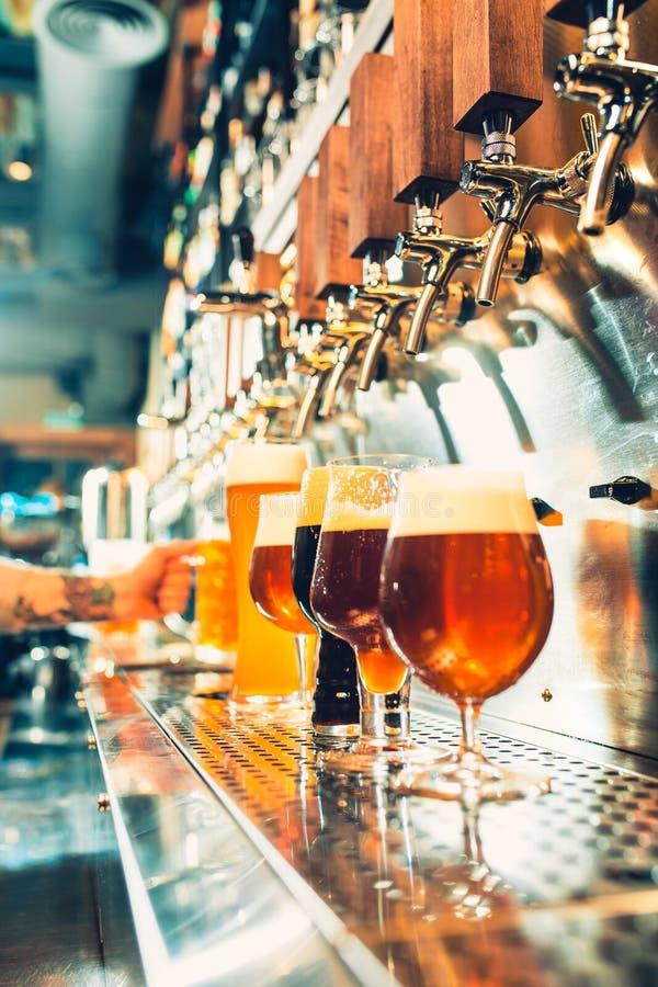 Hand av bartendern som häller ett stort lageröl i klapp arkivfoto