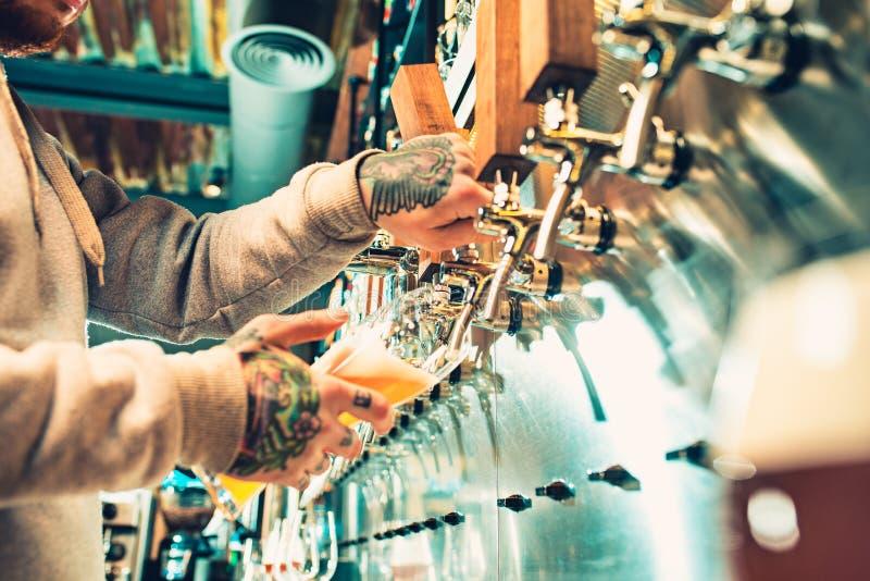 Hand av bartendern som häller ett stort lageröl i klapp arkivbild