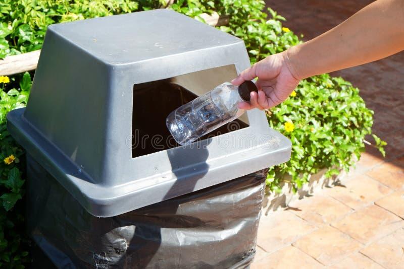 Hand av den asiatiska kvinnan som kastar en tom plast- flaska av dricksvatten in i ett allmänt grått avfallfack på vandringsledet arkivfoton