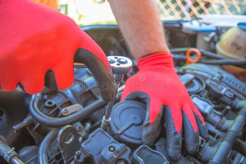 Hand av den auto mekanikern med en skiftnyckel Motorreparation Kontrollera av en bilkapacitet i bil-omsorg service royaltyfri bild